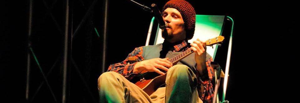 Na zdjęciu aktor Wojciech Chowaniec gra na ukulele i opowiada poetyckie historie.