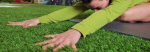 Czarnowłosa kobieta w pozycji dziecka wyciąga daleko przed siebie dłonie rozczapierzając je na trawie.
