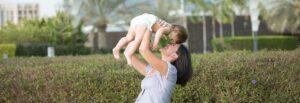Ciemnowłosa uśmiechnięta mama unosi nad sobą radosne potomstwo. Siedzą razem na trawie wygrzewając się na słońcu.