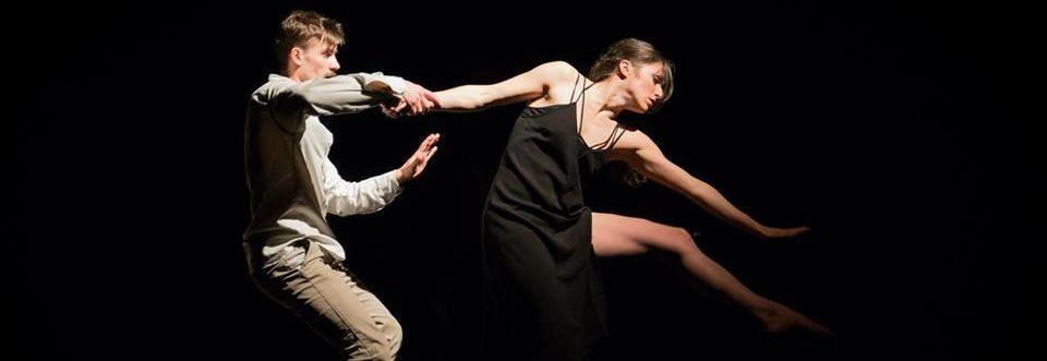 Mężczyzna tańczy z kobietą trzymając ją za rękę. Kobieta jest w zawieszeniu i szuka czegoś po przeciwnej stronie tancerza.