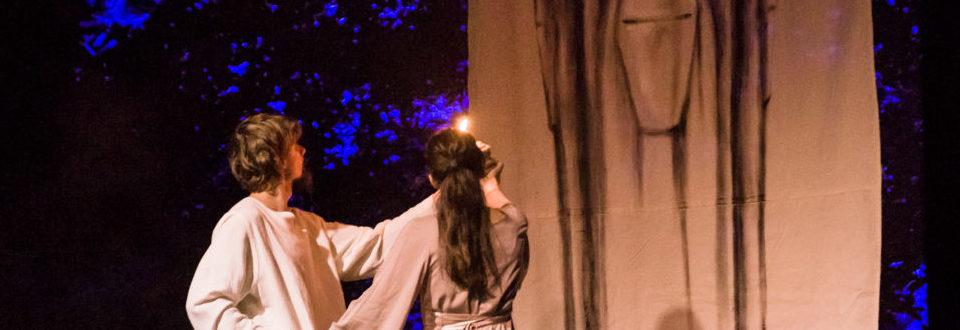 Na zdjęciu para trzyma się za ręce i podświetla obraz pogańskiego bóstwa.